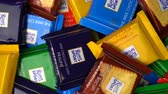 pražený ořech : Samara, Russian Federation - August 13, 2018: Ritter sport chocolates mini rotate background. Ritter Sport - a popular German brand of chocolate, which is sold in many countries of the world. Dostupné videozáznamy
