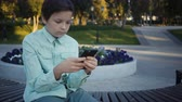 película de filme : teenager playing video games on his smartphone outdoors.