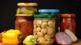 enlatado : Footage glass jars with salted vegetables for the winter rotated on table.