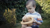 suporte : footage farm boy holding a small chick in the hands outdoor.