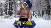 young girl rolling on tubing in the park in winter. Wideo