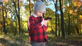 boy is playing game on smartphone in autumn park.