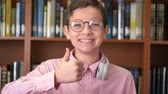 portrait shot of the cute schoolboy standing near the bookshelf in the library and doing thumb up Stock mozgókép