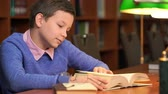 portrait of schoolboy doing their homework in library or room. Стоковые видеозаписи