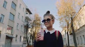 Pretty hipster teen with red bag drinks milkshake from a plastic cup walking street between buildings. Cute girl in sunglasses drinks a beverage through a straw.