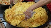 есть : Chinese noodles with chicken and vegetables. Frying noodles on a large pan. Street food at the stand. Стоковые видеозаписи
