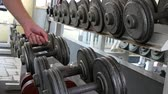 mide : Exercise in the gym. Fitness machines and aids. Choosing the right weight of the dumbbells.