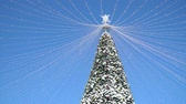 Big Outside Decorated Christmas Tree Towering into a Blue Sky on a Sunny Day with Passing White Clouds in Orlando Florida Vídeos