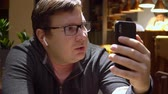 Man Make Online Video Call Using phone and wireless earpnones in restaurant blogger freelancer