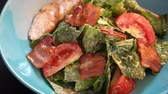 Lettuce, tomatoes and chicken breast salad in blue plate in restaurant healthy clean eating concept slow motion slider