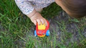 speelgoedauto : A small girl toddler or baby in dress playing outdoors with plastic car toys, childhood activity Stockvideo