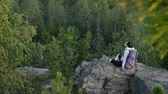 comprometido : Young woman backpacker sitting on big rock and relax ar sunrise