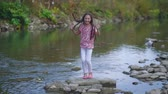 para : Happy little girl jumping on the rocks near the river. Stock Footage