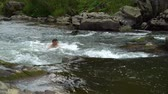 The guy is swimming in the river. A young cute guy bathes in a clean mountain river. He is happy.