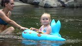 Mom and daughter in the river. A young beautiful woman is bathing in a mountain river with her little daughter. They are having fun and laughing. The girl is floating on an inflatable circle. Stock Footage