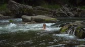 Woman bathing in the river. A young nice woman is bathed in a clean mountain river. She is happy.