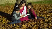 trpělivost : Mom and children are sitting under a tree and reading a book. Mom and children in the autumn forest. They are happy. Dostupné videozáznamy