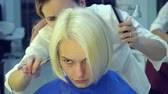 narzedzia fryzjerskie : Beauty saloon. Barbershop. Stylist hairdresser cuts hair young girl. The stylist uses scissors and a comb. Close-up. Slow motion.