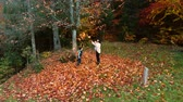 acero : Young beautiful mother and her little son have fun in the autumn forest. They jump and throw leaves into the air. They are laughing. The family is happy. Slow motion. Slow motion.