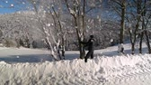 sacudindo : A young man walks through a snowy mountain forest. He shakes snow from a tree. He is happy and laughing fun. Slow motion. Stock Footage