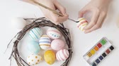 Coloring eggs for Easter with hands and a brush with watercolor paints. Nest and wreath.