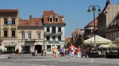 piata : BRASOV, ROMANIA - AUGUST 21: Tourists stroll at main square on August 21, 2012 in Brasov, Romania. Brasov is a popular tourism destination with 581,983 arrivals in Brasov County in 2008.