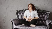 umma : Attractive pregnant woman with the red hair. Sitting on a vintage sofa and laughs. Slow motion