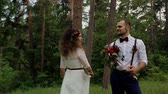 wedding : Beautiful young hipster couple curly bride posing in forest. The groom holds in his hands a magnificent bouquet.