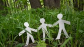 Concept of person and environment. Human figures made of paper on grass. Static camera video footage HD. Wideo