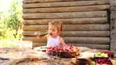 Cute little boy in white pinafore eats fruit cake and cup of milk at table outdoors on wooden.