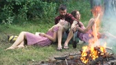 lenha : Happy friends playing music and enjoying bonfire in nature. Teenagers having fun at the forest. Friends sitting in the forest in circle around a camp fire. Stock Footage