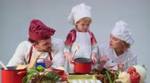 omini : Family cooking kitchen food fogetherness concept. Family cooking meal In kitchen together. Cute little boy and his handsome dad cutting vegetables and smiling while cooking in kitchen at home. Filmati Stock