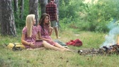 Happy friends playing music and enjoying bonfire in nature. Teenagers having fun at the forest. Friends sitting in the forest in circle around a camp fire. Dostupné videozáznamy