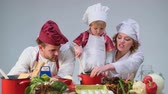 Family cooking kitchen food fogetherness concept. Family cooking meal In kitchen together. Cute little boy and his handsome dad cutting vegetables and smiling while cooking in kitchen at home Dostupné videozáznamy