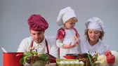 omini : Cute little boy and his beautiful parents are smiling while cooking in kitchen. Young family cooking food in kitchen. Happy family cooking together. Happy young family with Mum, Dad child cooking