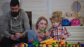 bloco : Young family play game with construction plastic blocks. Family games concept. Parents and kid with happy faces hold red bricks. Father, mother and son in playroom on light wooden background.