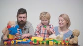 parentalidade : Young family play game with construction plastic blocks. Family games concept. Parents and kid with happy faces hold red bricks. Father, mother and son in playroom on light wooden background