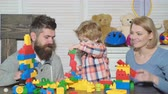 bloco : Young family in playroom. Love family concept. Mom, dad and boy with toys build out of plastic blocks. Parents and son smiling, make brick constructions.
