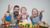 bausteine : Young family play game with construction plastic blocks. Family games concept. Parents and kid with happy faces hold red bricks. Father, mother and son in playroom on light wooden background.