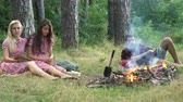lareira : Happy friends playing music and enjoying bonfire in nature. Teenagers having fun at the forest. Friends sitting in the forest in circle around a camp fire. Stock Footage