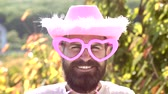 vaqueiro : Comic man with funny hipster pink sunglasses and comic pink hat. Bearded crazy man looking at the camera. Make funny face. Cowboy.