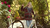 novembro : Dreamy girl with long hair in knit sweater. Romantic Young Woman on spring Background Outdoors. Autumn happy people and joy. Beautiful smiling girl is riding the bicycle in the park. Stock Footage