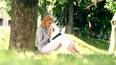 sentar se : Girl makes notes in a notebook while sitting in the park on the grass. Student is studying in a park.