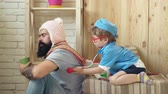 pediatrician : Happy healthy child is played by a doctor. Doctor and his patient. Boy dressed in a doctor listens to a patient with a stethoscope.