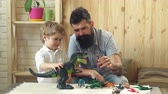 plástico : Man and boy play together on wooden wall background. Family and childhood concept. Father and son play with toys dinosaurs.