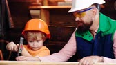 nehty : Father and son in protective helmets hammer a nail into a board. Father teaches his son a building affair. Dostupné videozáznamy