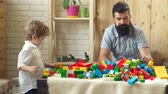 bloco : Father and son with happy faces create colorful constructions with toy bricks. The boy and his father play with the designer bricks. Family and childhood concept. Stock Footage