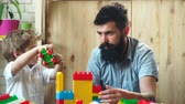 plástico : Boy and bearded man play together. Family and childhood concept. Father and son create colorful constructions with toy bricks. Dad and kid build house of plastic blocks. Stock Footage