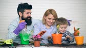 creuser : Concept of gardening. The family in game form planting and watering flowers. A little boy and his parents water flowers.