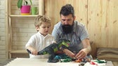 desenvolver : Father and son play with dinosaurs. Adorable little child plays with his bearded father with plastic dinosaurs. Father and cute little son playing toy dinosaurs on tabletop together at home.